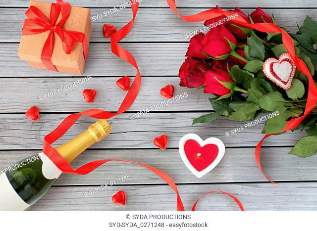 close up of champagne, gift, candies and red roses