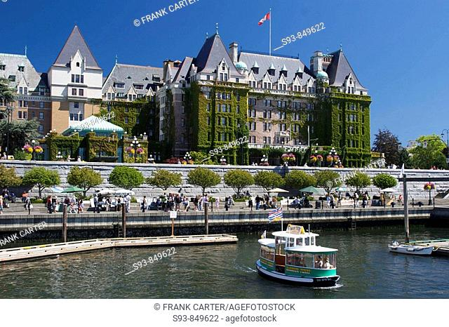 A view of Victoria, British Columbia's inner harbour, showing the ivy covered Empress Hotel, a small harbour ferry, and tourists enjoying the sights and events...