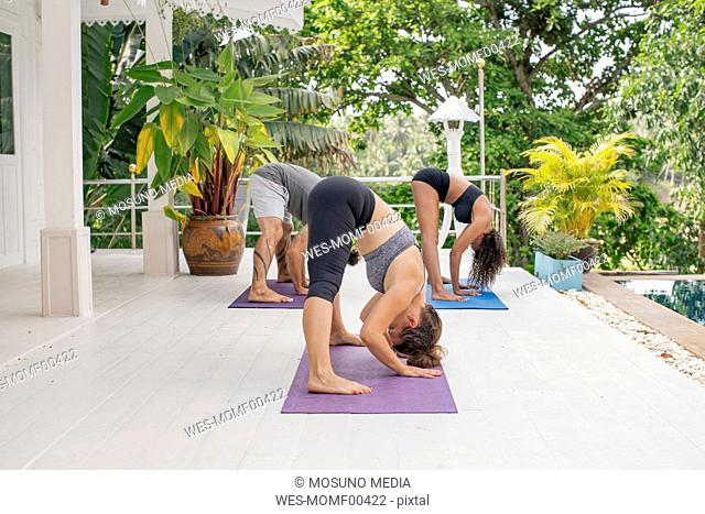 Two women and a man practicing yoga on terrace