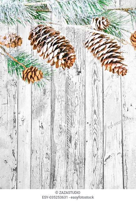 Christmas background with fir branches,pinecones and berries on the old wooden board in vintage style