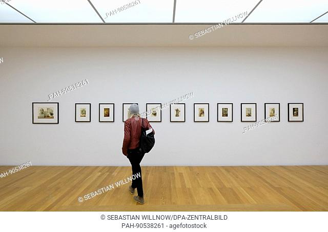 Awoman looks at paintings illustrating selected after-dinner speeches of Martin Luther by Michael Triegel at the Museum for Visual Arts ('Museum der Bildenden...
