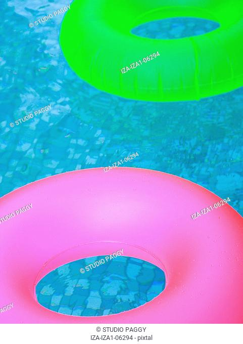 High angle view of two inflatable rings floating in a swimming pool