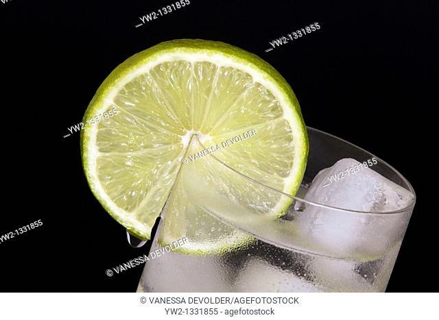 Lime slice on a glas  Studio photograph, black background  V10BEL0514