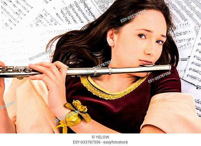 the girl in a brocade dress with a flute on the background of the notes