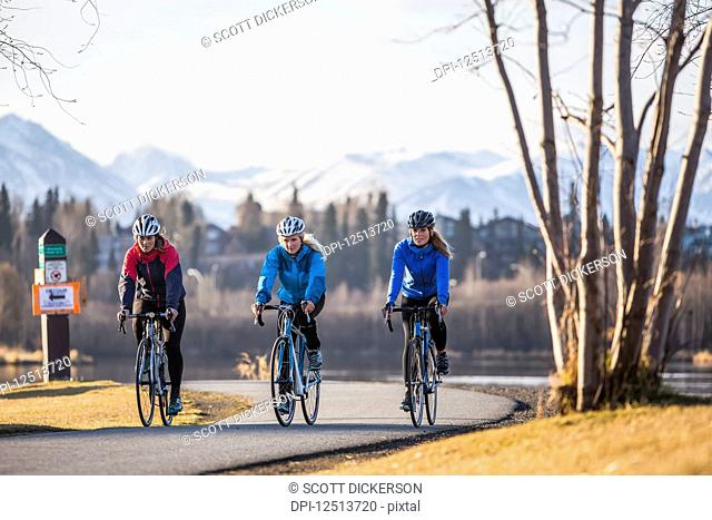 Three young women riding their bicycles on a trail along the water's edge; Anchorage, Alaska, United States of America