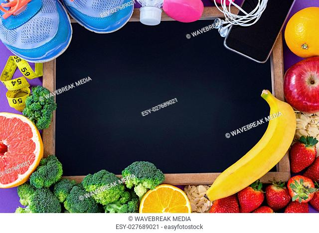 Slate surrounded with fitness accessories and various fruits and vegetables