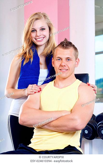 portrait of fit young woman and man in modern gym