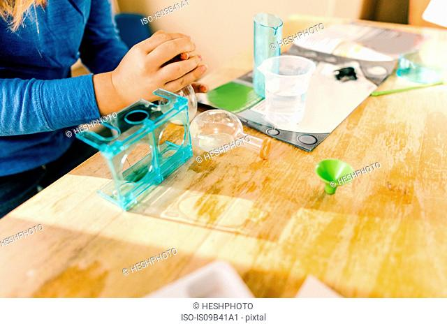Hands of girl preparing to do science experiment at table