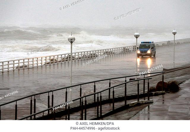 A police car drives next to the beach in Westerland on the isle of Sylt, Germany, 05 December 2013. Storm front Xaver has reached the North Sea coast of Germany