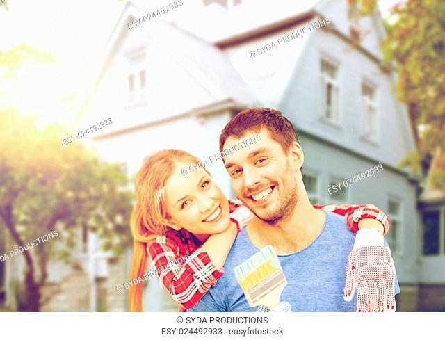 repair, building and home concept - smiling couple covered with paint with paint brush