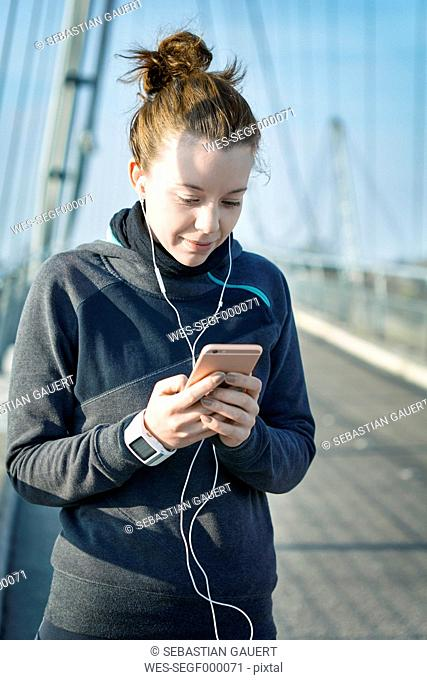 Portrait of young female jogger with heart rate monitor, earphones and smartphone hearing music