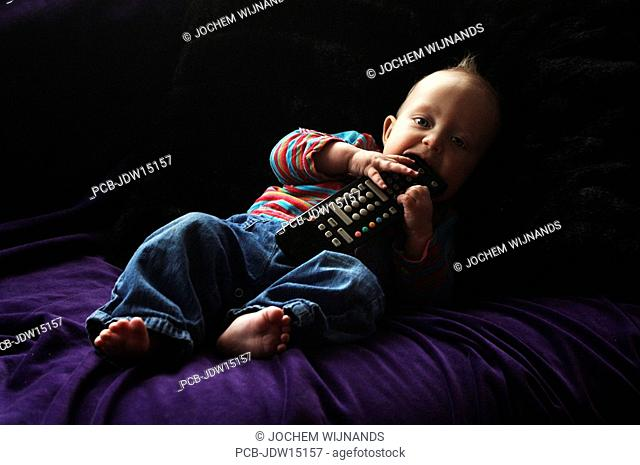 Six month old baby boy with the remote control on the couch