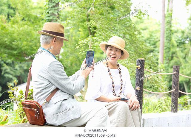 Senior couple taking photos with smart phone