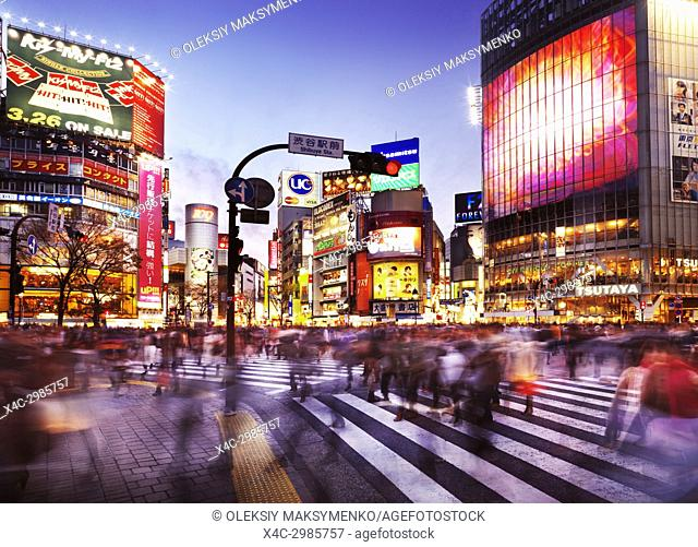 Crowd of people crossing Meiji dori street at Shibuya station busy intersection lit with colorful signs and ads in the evening rush hour