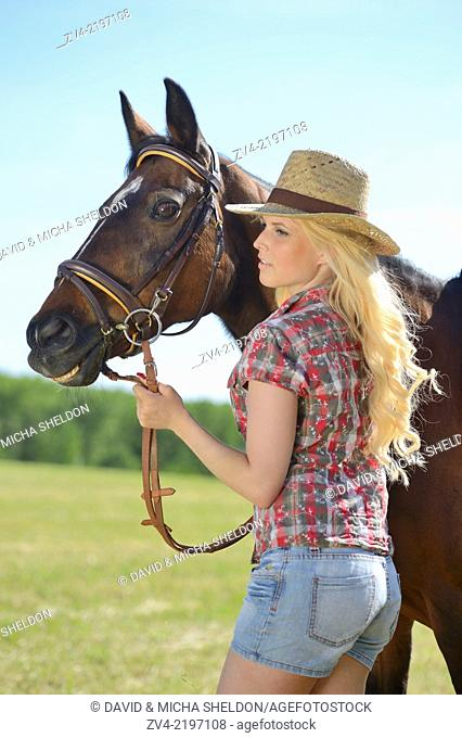Young cowgirl standing beside a polish arabian horse
