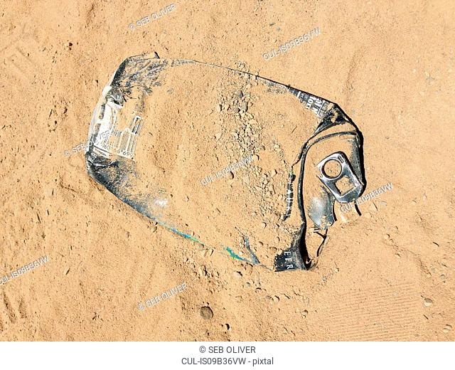 Overhead view of squashed drinks can in sand