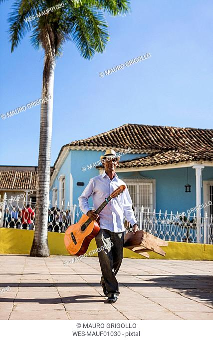 Cuba, walking man with guitar and stool on the street
