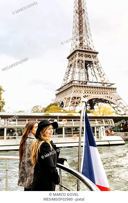 Paris, France, two tourists taking a cruise on Seine River with Eiffel Tower in the background