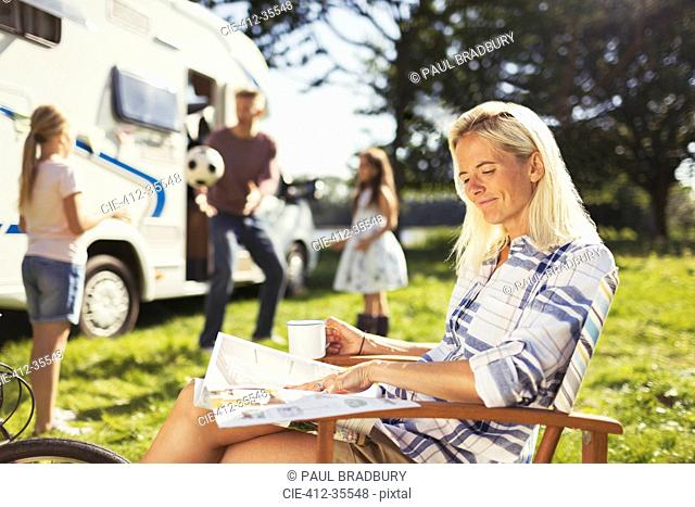 Smiling woman reading magazine and drinking coffee outside sunny motor home