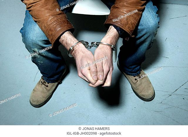 Picture shows a Handcuffed man in a police cell