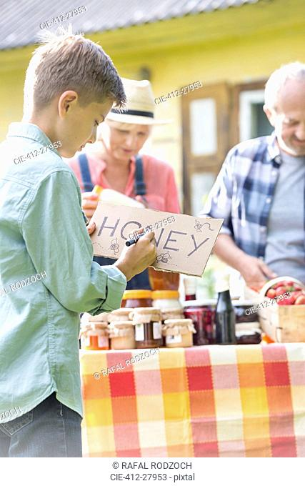 Boy drawing honey sign for farmer's market stall