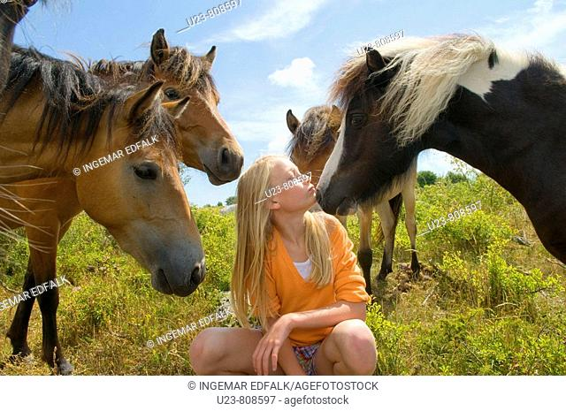 Small girl in a pony herd