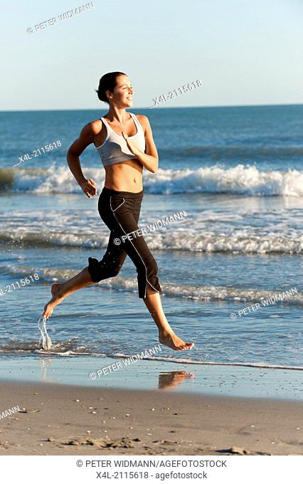 young, pretty, sportive woman on the beach, jogging (model-released)