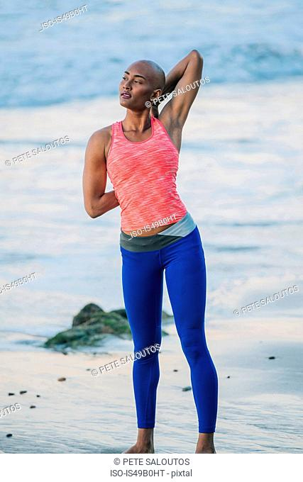 Young woman exercising, stretching, on beach