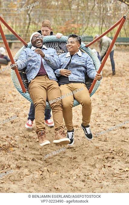 adult friends using swing on playground, fun, happy, in Munich, Germany