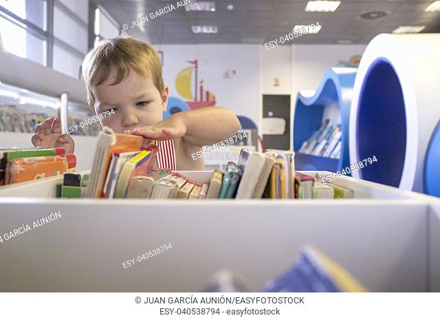 Inquisitive 2 years boy searching books at library. Discovering the books at his first visit at preschool library