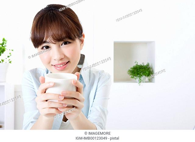 Young woman holding a coffee cup and smiling at the camera