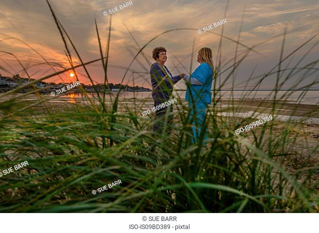 Woman and carer enjoying evening sunset by sea
