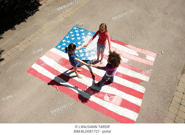 Girls holding hands in circle on chalk colored American flag