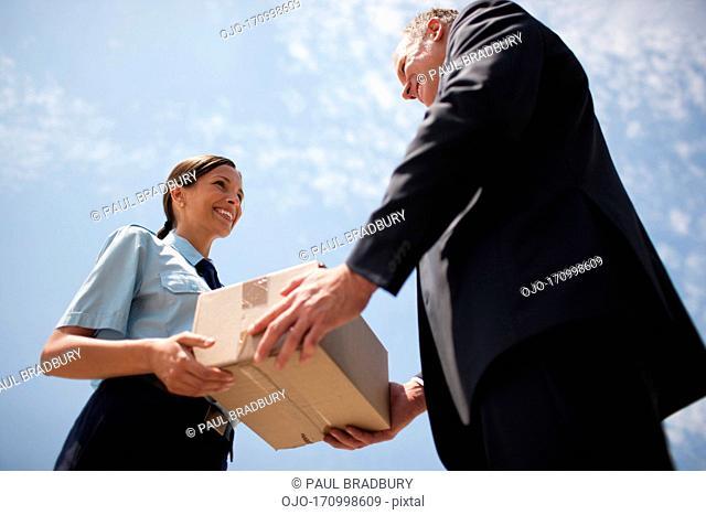 Supervisor handing box to worker