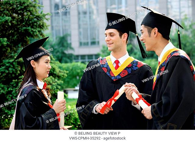 Three university students in graduation gown