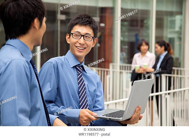 Businessmen working outside with laptop