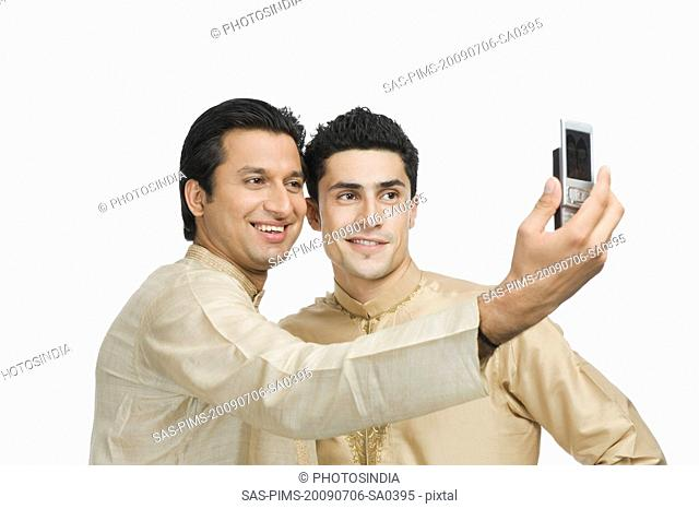 Two men taking a picture of themselves with a mobile phone