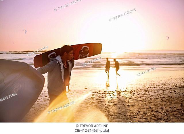 Man carrying kiteboard on sunset beach