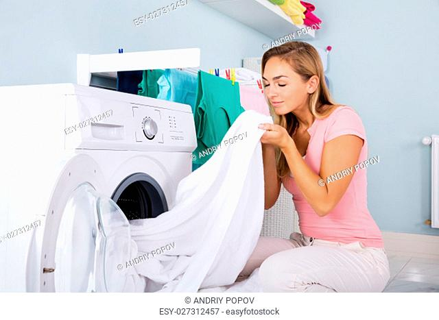 Young Woman Smelling Clean Clothes Near The Electronic Washer At Laundry Room