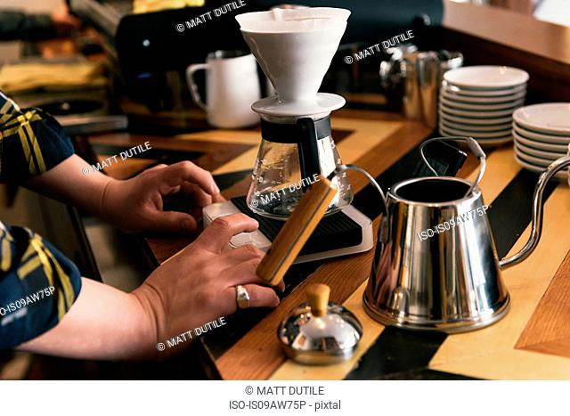 Close up of waiters hands preparing coffee filter at coffee shop counter