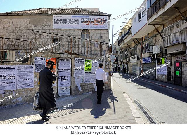 Banner up on a house with rules of conduct for tourists, wall newspapers and an Orthodox Jew with a mobile phone at the front in the district Me'a She'arim or...