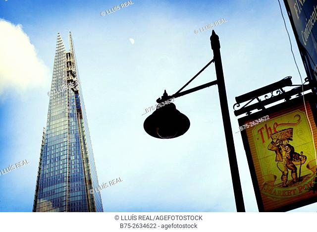 The top of the Shard building with the blu sky and the moon, a lamp post, and The Market Porter Pub sign. Borough Market, Southwark, London Bridge, London