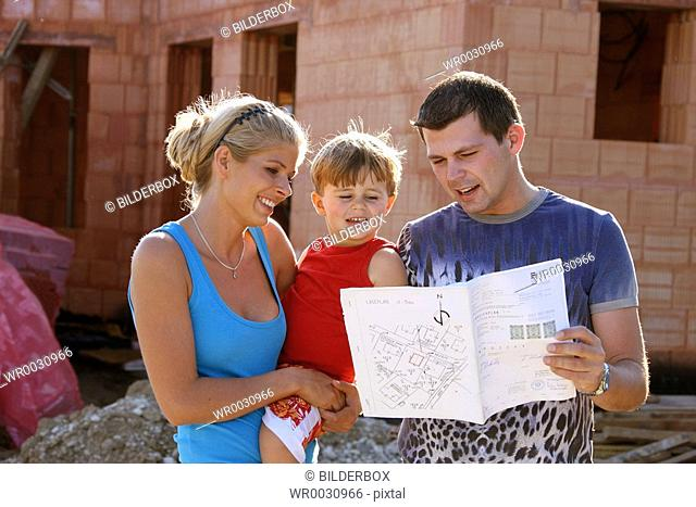 Family in front of shell of bulding