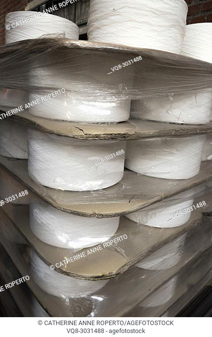 Confrontational flat industrial spools of white thread packaged with layers of thick corrugated card dividers and shrink wrapped in reflective polythene for the...