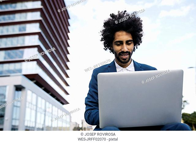 Spain, Barcelona, smiling young businessman sitting outdoors in the city working on laptop