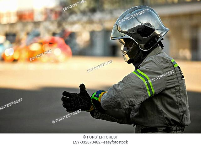 Rescuer in uniform adjusts protective glove and burning car on background
