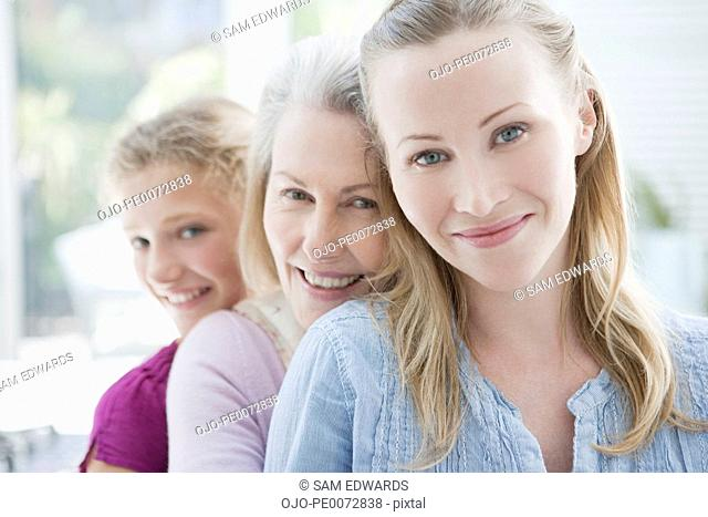 Smiling grandmother, mother and daughter hugging