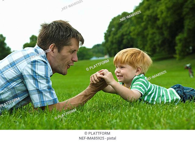 Father and son lying on lawn in park and playing