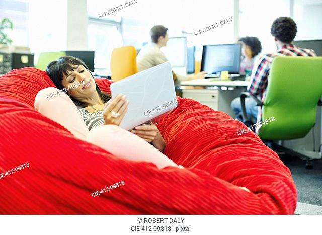 Businesswoman using laptop in bean bag chair in office