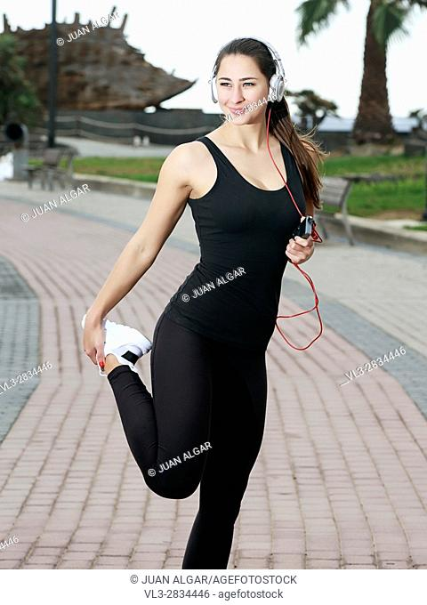 Woman stretching and listening to music